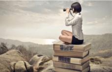 ragazza che siede su un libro